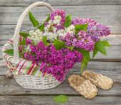 foto of bast  - White basket with lilacs and bast shoes on a wooden table - JPG