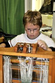 foto of handloom  - A young boy operating an old handloom - JPG