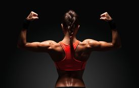 image of shoulder muscle  - Athletic young woman showing muscles of the back and hands on a isolated black background with clipping path - JPG