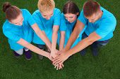picture of joining hands  - People joining their hands  on green grass  - JPG