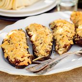 stock photo of crust  - Meat and Tomato Stuffed Eggplant Halves with Cheese Crust selective focus on the middle eggplant crust square - JPG