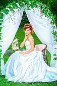 foto of wedding arch  - Beautiful bride with chaming red hair sitting under the wedding arch - JPG