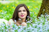 stock photo of forget me not  - Young woman is lying on field with forget - JPG