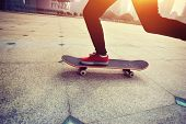image of skateboarding  - woman skateboarder legs skateboarding at sunrise city