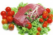 picture of veal meat  - fresh raw beef meat steak on green salad with cherry tomatoes - JPG