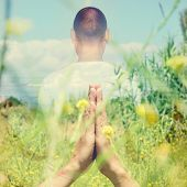 foto of mudra  - double exposure of a young caucasian yogi man in meditating outdoors with his hands in anjali mudra - JPG