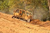 stock photo of bulldozer  - Exchavator bulldozer pushes top soil and loose dirt down a hill at a new commercial construction development project - JPG