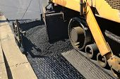 stock photo of construction machine  - A paver finisher asphalt finisher or paving machine placing a layer of asphalt during a repaving construction project - JPG
