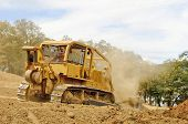foto of bulldozer  - A large bulldozer spreads dirt and rock for a new fill layer on a commercial construciton road project - JPG