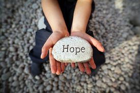 stock photo of carving  - Child on a beach with hands cupped holding stone pebble with the word hope engraved concept for faith - JPG