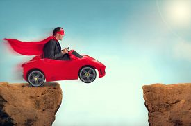stock photo of ravines  - man in a red car jumping a ravine - JPG