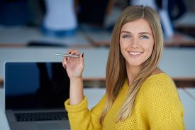 stock photo of classroom  - portrait of happy smilling student girl at tech classroom with laptop computer in background - JPG