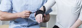 picture of stability  - Male physiotherapist is putting stabilizer on patient hand - JPG