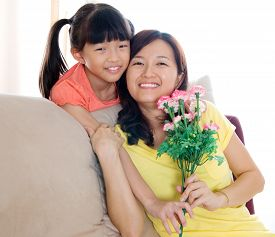 picture of carnations  - Asian girl giving carnation flower to mother on mothers day - JPG