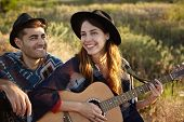 Smiling Glad Couple Enjoying Their Rest Outdoors Sitting At Green Grass Of Meadow Playing Guitar Lis poster