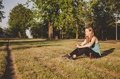 Relaxing Outdoor. Young Woman Sitting In The Park, Relaxing After Running And Using Her Smartphone. poster