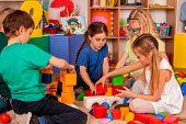 Children building blocks in kindergarten. Group kids playing toy on floor in interior preschool. Bui poster