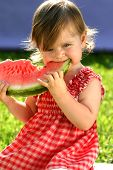 stock photo of healthy eating girl  - Littele girl in red dress eating watermelon - JPG