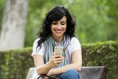 Happy Attractive Latin Woman Talking And Texing On Her Smart Phone. poster