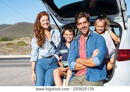 poster of Smiling family with two kids sitting in car trunk and looking at camera. Happy children enjoying wit