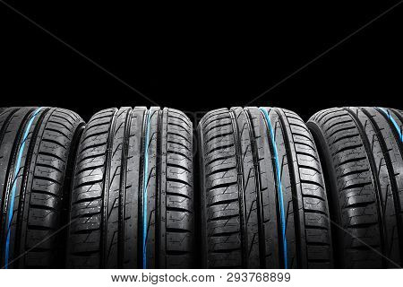 poster of Studio Shot Of A Set Of Summer Car Tires On Black Background. Tire Stack Background. Car Tyre Protec