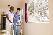 Front view of Asian female nurse helping senior Caucasian male patient to walk with walker in corrid poster