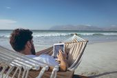 Rear view of young Caucasian man using digital tablet while lying on hammock at beach on sunny day poster