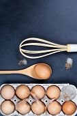 Eggs, wooden spoon, whisker and feathers. Kitchen utensil for cake, pastry or cookies on backboard b poster