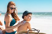 Happy mother in blue bikini sitting on beach applying sunblock cream on sons shoulder with copy spa poster