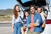 Smiling family with two kids sitting in car trunk and looking at camera. Happy children enjoying wit poster