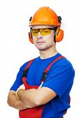 Portrait of young builder in protective safety equipment goggles hard hat earmuffs isolated