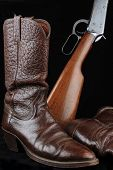 stock photo of caribou  - Pair of caribou hide cowboy boots and western lever - JPG