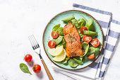 Keto Diet Food. Baked Salmon Fish Fillet With Fresh Salad From Spinach And Tomatoes. Top View On Whi poster