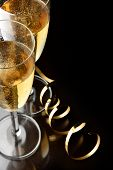 stock photo of champagne glasses  - Couple glasses of champagne with gold streamer and space for your own text on right - JPG