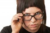 stock photo of headstrong  - Serious female teenager looking over her eyeglasses - JPG