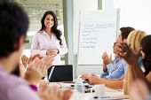 stock photo of applause  - Businesswoman Addressing Meeting Around Boardroom Table - JPG