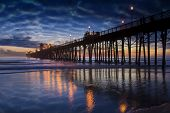 Oceanside Pier with layered clouds reflected in tidal waters of the Pacific Ocean. Oceanside is 40 m