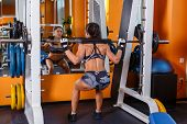 pic of squatting  - Beautiful young sports woman doing squats with a barbell in Smith Machine in the gym - JPG