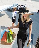 Rich woman carrying shopping bags while boarding private jet with pilot and airhostess in background