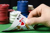 picture of poker hand  - hand in foreground holding pair of kings in poker - JPG