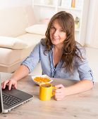 Beautiful young woman eating cornflakes and drinking coffee while working with laptop