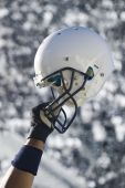 stock photo of football helmet  - A football player raises his helmet in triumph and celebration during an american football game - JPG