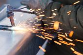 foto of pipe-welding  - worker cutting steel pipe using metal torch and install roadside fence - JPG