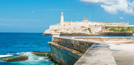 picture of malecon  - The castle of El Morro in Havana and the famous  wall of Malecon with white puffy clouds on a blue sky - JPG