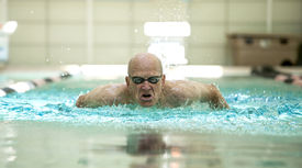 image of breast-stroke  - senior man swimming competitively in pool - JPG