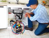 stock photo of plumber  - Plumber with Plumbing tools on the kitchen - JPG