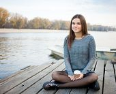 pic of jeans skirt  - Young beautful brunette woman in blouse and denim skirt sitting on the river pier with coffee and her smartphone - JPG