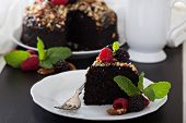 stock photo of tort  - Chocolate banana cake with nuts decorated with berries - JPG