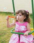 picture of seesaw  - cute little girl swinging on seesaw and playing with soap bubbles - JPG