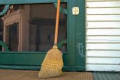 stock photo of hobo  - Old worn out broom leaning on a green door with hobo sign - JPG